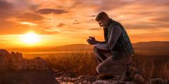 En man som ber på knä ute i naturen