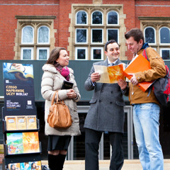 Pawel and Esther Pyzara stand by a literature display cart and speak to a man about the Bible