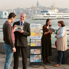 Jehovah's Witnesses stand by a literature display cart and share in public witnessing