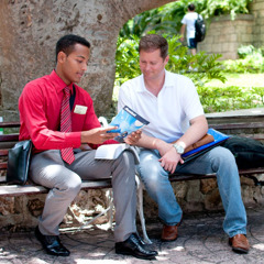 One of Jehovah's Witnesses preaches to a man on a park bench