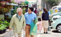 एक बुज़ुर्ग आदमी वॉकर के सहारे चल रहा है और एक जवान उसका समान उठाए हुए है