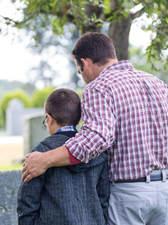 A father and his young son at a cemetery