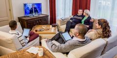 Vanhempi pariskunta katsoo JW Broadcasting -lähetystä nuoren perheen kanssa