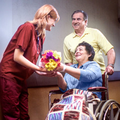 A couple give a health-care worker a bouquet of flowers