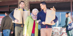 Two young brothers carry bags of groceries for an elderly sister