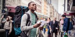 한 젊은 남자가 외국에서 길을 찾으려고 애쓰는 모습