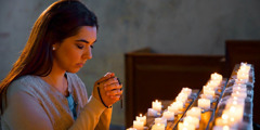 A woman prays with a rosary in front of burning candles