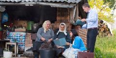 Румынире старейшинӑпа унӑн арӑмӗ ҫӑм чавса ларакан икӗ хӗрарӑма ырӑ хыпар пӗлтереҫҫӗ