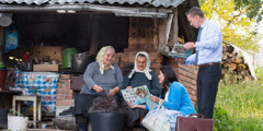 An elder and his wife in Romania preach to two women who are combing wool from sheep