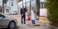 Seorang ayah menemani putrinya yang sedang memberikan risalah kepada orang di jalan