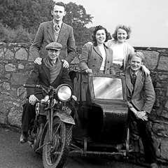 Arthur and Olive Matthews with fellow pioneers on a motorcycle and sidecar