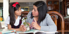 A mother teaches her daughter about Jehovah as they look at a plant together