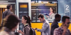 A woman reads the Bible while on a train, and others rush through the train station