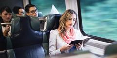 Una dona llegint la Bíblia al tren