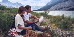 A couple reads the Bible while on a picnic