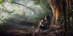A girl sits alone in a forest and sadly looks up at the sky