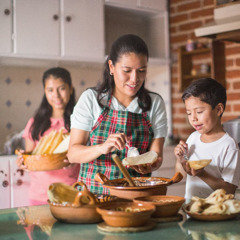 A mother and her children prepare food for guests