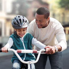 A father teaches his son to ride a bicycle