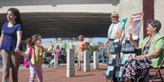 Sergio y Olinda ofrecen publicaciones bíblicas a las personas cerca de una parada de autobús