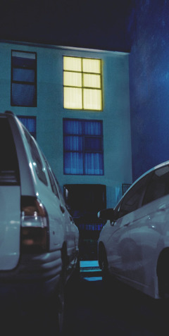 Two cars parked outside a residence at night