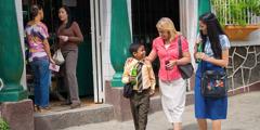 एउटी आमा र तिनका छोराछोरी प्रचारकार्यमा भाग लिँदा चिसो पिउँदै