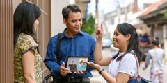 Uma irmã oferecendo a uma mulher a brochura Boas Notícias de Deus para Você!