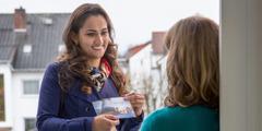 Uma irmã mostrando para uma mulher o convite para as reuniões