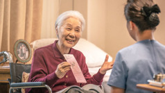 An older wheelchair-bound sister offers a tract to a health-care provider