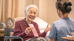 Một chị lớn tuổi ngồi xe lăn mời một người chăm sóc y tế nhận tờ chuyên đề
