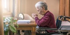 Pyörätuolissa oleva iäkäs sisar rukoilee