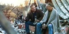 Two men sit among the rubble of a devastated building