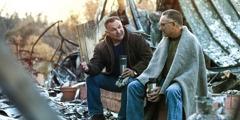 Zwei Männer sitzen zwischen den Trümmern eines Gebäudes