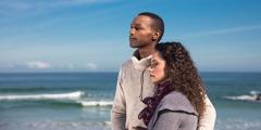 Ein trauerndes Paar steht dicht beieinander am Strand und schaut in die Ferne