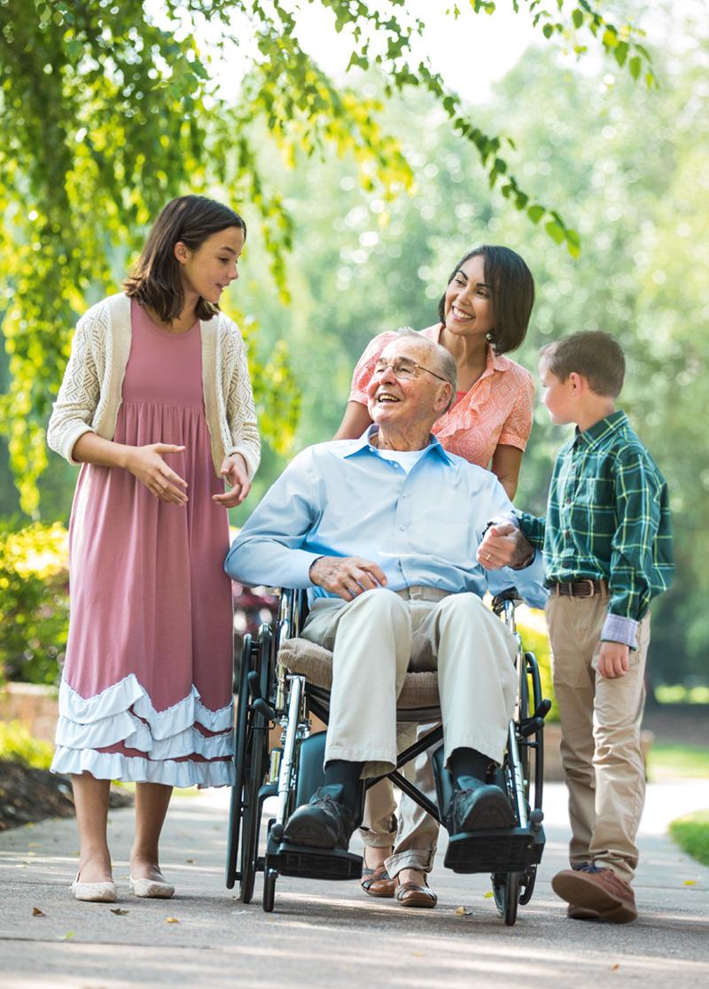 Un hombre enfermo en silla de ruedas rodeado por sus seres queridos