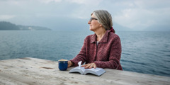 Uma mulher segura uma Bíblia aberta, sentada à mesa e olhando ao longe