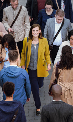 A young woman smiles and confidently walks along a crowded sidewalk