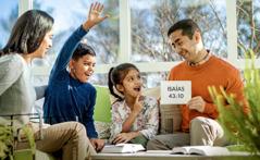 Durante la adoración en familia, unos padres utilizan tarjetas para ayudar a sus hijos a aprender de memoria textos bíblicos