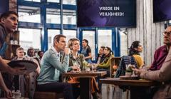 De klanten in een koffiehuis kijken gespannen naar een nieuwsbericht op tv over een aankondiging van 'vrede en veiligheid', maar een Getuigenechtpaar laat zich niet op het verkeerde been zetten