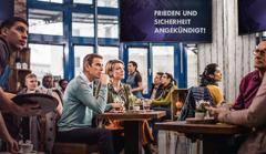 """Gäste in einem Café sind überrascht, als sie aus einer Eilmeldung im Fernsehen erfahren, dass """"Frieden und Sicherheit"""" verkündet wird. Ein Ehepaar lässt sich dadurch nicht täuschen. Die beiden sind Zeugen Jehovas"""