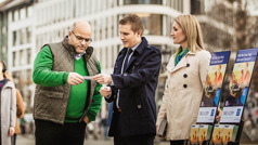 A man accepts a piece of literature from a couple at a public witnessing cart