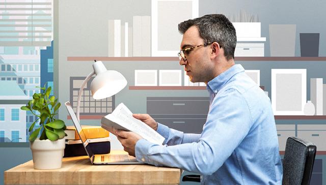 El mismo hombre leyendo la Biblia y con una computadora encendida