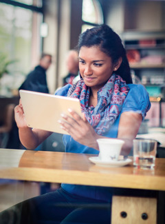 A young woman in a café reads the Bible on her electronic device