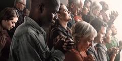 Des gens de races et d'âges différents prient.