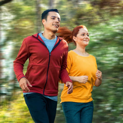 A couple jogging in a wooded area.
