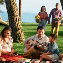 A family enjoying a picnic in a park. The father is playing a guitar.