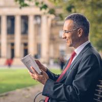 Κάποιος άντρας διαβάζει τη Γραφή ενώ κάθεται σε ένα παγκάκι μπροστά από κάποιο κυβερνητικό κτίριο.
