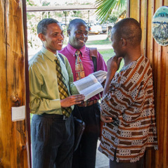 Two brothers in the door-to-door ministry share a scripture with a man