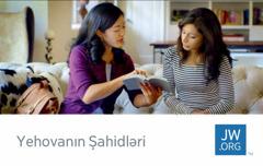 jw.org saytının vizit kartının üzərindəki şəkildə Yehovanın Şahidi qadına ayə oxuyur