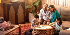 عائلة تستمتع بقضاء الوقت معا. الوالدان جالسان على كنبة يمسك احدهما بيد الآخر، فيما يرسم ابنهما وبنتهما صورا على طاولة القهوة.