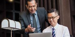 Un empresario dictándole una carta a su secretario, que la escribe en su computadora portátil